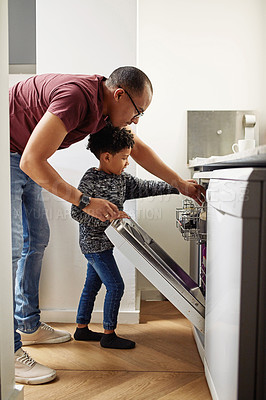 Buy stock photo Shot of a young father and young son both reaching into a dishwasher to remove dishes