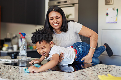 Buy stock photo Shot of a smiling young mother holding her son stretched across a kitchen counter while he wipes it