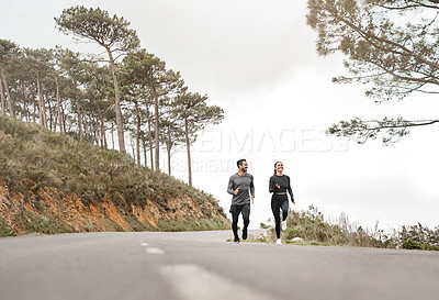 Buy stock photo Full length shot of two young athletes bonding together during a run outdoors