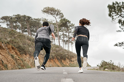 Buy stock photo Full length shot of two unrecognizable athletes bonding together during a run outdoors