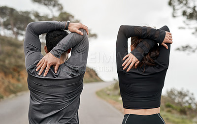 Buy stock photo Cropped shot of two unrecognizable athletes stretching before exercising outdoors together