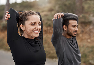 Buy stock photo Cropped shot of two young athletes stretching before exercising outdoors together