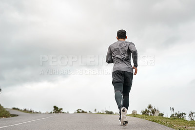 Buy stock photo Full length shot of an unrecognizable man jogging alone outdoors