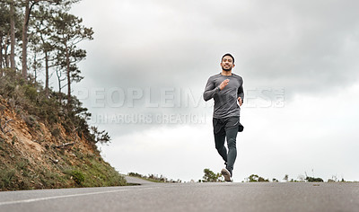 Buy stock photo Full length shot of a handsome young man jogging alone outdoors