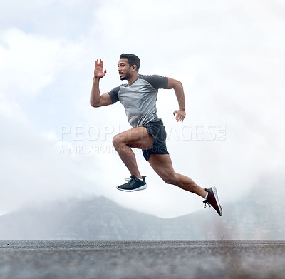 Buy stock photo Full length shot of a handsome young man jumping during a workout outdoors