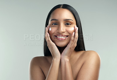 Buy stock photo Shot of a beautiful young woman applying moisturiser to her skin