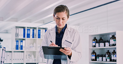 Buy stock photo Shot of a young woman writing notes on a clipboard in a lab
