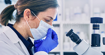 Buy stock photo Shot of a young woman using a microscope in a lab