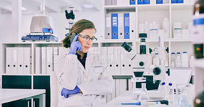 Buy stock photo Shot of a young woman talking on a cellphone in a lab