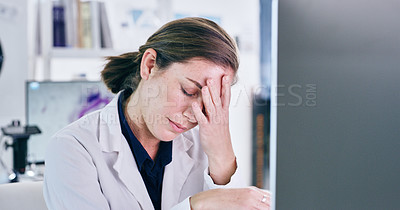 Buy stock photo Shot of a young woman looking stressed out while working on a computer in a lab