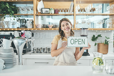 Buy stock photo Portrait of a young woman holding up an open sign in her cafe