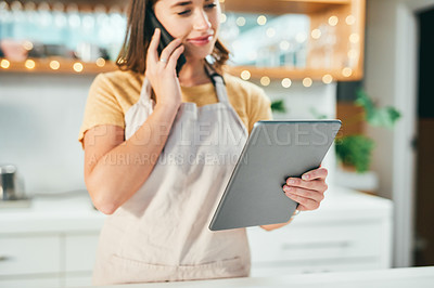 Buy stock photo Shot of a young woman using a digital tablet and smartphone while working in a cafe