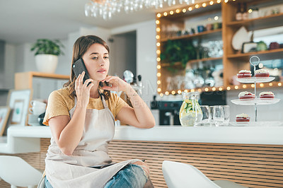 Buy stock photo Shot of a young woman using a smartphone and looking worried while working in a cafe