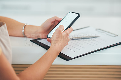Buy stock photo Shot of a woman using a smartphone while going through paperwork in a cafe