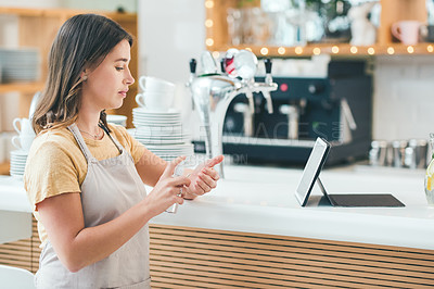 Buy stock photo Shot of a young woman disinfecting her hands while working in a cafe