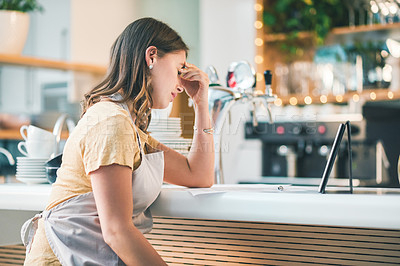 Buy stock photo Shot of a young woman experiencing stress while working in a cafe