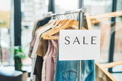 Buy stock photo Shot of a sale sign hanging on a clothing rack in an empty boutique