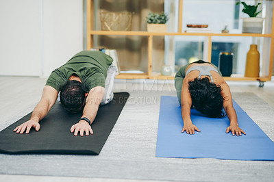 Buy stock photo Shot of a young couple doing yoga together at home