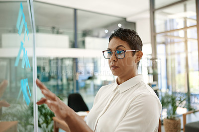 Buy stock photo Shot of a mature businesswoman brainstorming with notes on a glass wall in an office