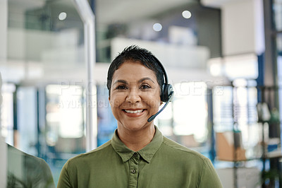 Buy stock photo Portrait of a mature businesswoman wearing a headset in an office