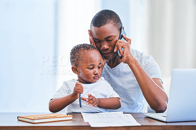 Buy stock photo Shot of a young man looking stressed while using a smartphone with his baby son sitting on his lap at home