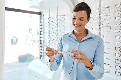 Buy stock photo Shot of an optometrist measuring a pair of glasses with a pd ruler