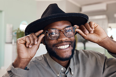 Buy stock photo Shot of a young man buying a new pair of glasses at an optometrist store