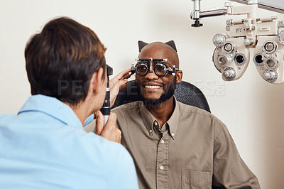 Buy stock photo Shot of an young man getting new glasses fitted by an optometrist