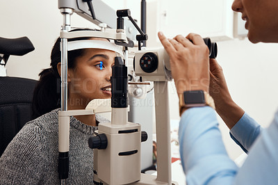 Buy stock photo Shot of a young woman getting her eye's examined with a slit lamp