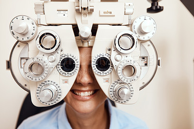 Buy stock photo Shot of a young woman getting her eye's examined with an optical refractor