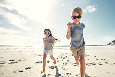 Buy stock photo Shot of a little boy and a girl  running together on the beach