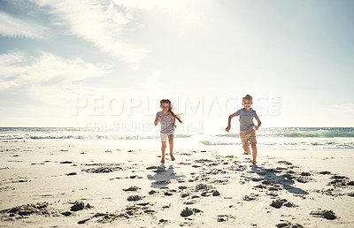 Buy stock photo Shot of a little girl and a boy running together on the beach