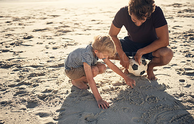 Buy stock photo Shot of a man and his son playing Tic Tac Toe in the sand on the beach