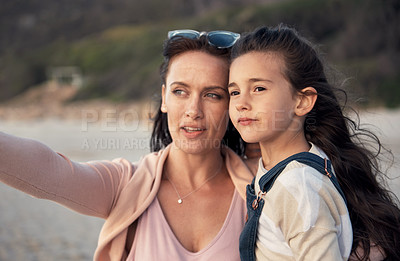 Buy stock photo Shot of a woman and her young daughter spending quality time at the beach