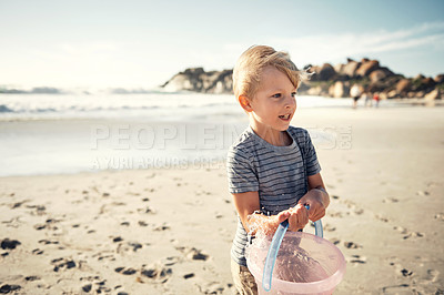 Buy stock photo Shot of a little boy holding a bucket with water on the beach