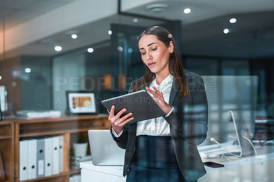 Buy stock photo Cropped shot of an attractive young businesswoman standing alone in her office at night and using a tablet