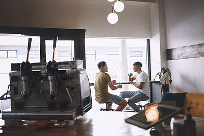 Buy stock photo Shot of two young men sitting together in a coffee shop