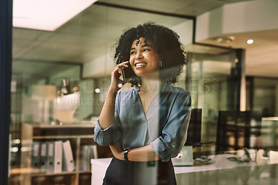 Buy stock photo Shot of a young businesswoman using a smartphone during a late night at work