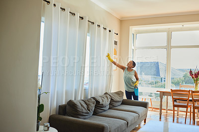 Buy stock photo Shot of a young woman cleaning the living of her apartment