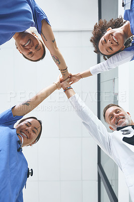 Buy stock photo Low angle portrait of a diverse group of healthcare professionals standing and giving each other a high five