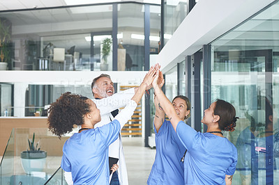 Buy stock photo Cropped shot of a diverse group of healthcare professionals standing and giving each other a high five