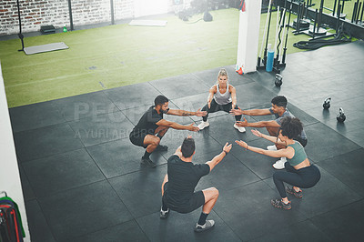 Buy stock photo Shot of a fitness group squatting as part of their exercise routine at the gym