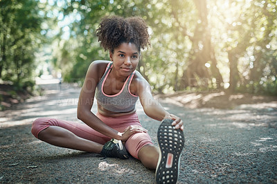 Buy stock photo Shot of a beautiful young woman stretching before her run