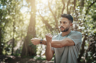 Buy stock photo Shot of a young man warming up before his workout