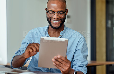 Buy stock photo Cropped shot of a handsome young businessman sitting alone in his office and using a digital tablet