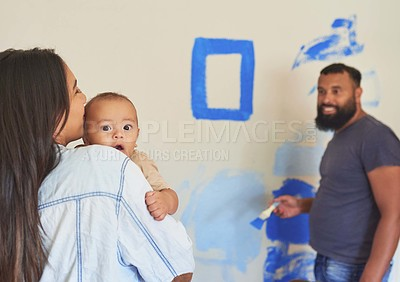 Buy stock photo Shot of a woman holding her baby while watching her husband paint a room at home
