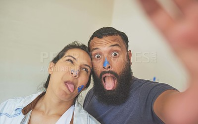 Buy stock photo Shot of a playful couple taking a selfie with paint on their faces while painting at home