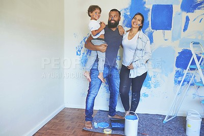 Buy stock photo Shot of a couple and their son standing together while painting a room blue
