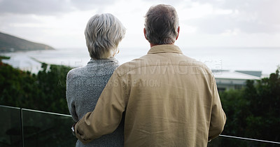 Buy stock photo Rearview shot of a happy senior couple standing together on a balcony and looking at the ocean view