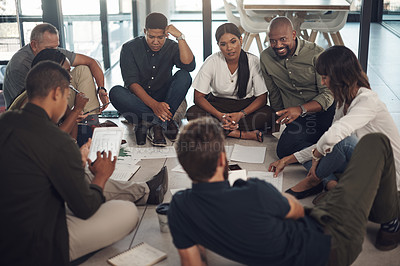 Buy stock photo Shot of a diverse group of businesspeople brainstorming with notes on a floor in an office